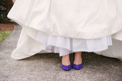 Wedding dress legs purple shoes. Stock Image