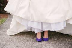 Wedding dress legs purple shoes. Stock Image