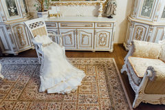 Wedding dress lying on a chair in the room Royalty Free Stock Photo