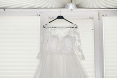 Wedding dress perpared for the bride. Wedding dress with tulle skirt and lace  hanging on a hanger Stock Photo