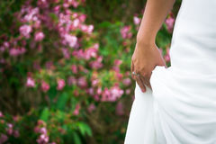 Wedding Dress and Ring on Bride in Garden Close-up With Copyspac. Close-up of bride`s hand and dress in garden with floral background and copyspace Stock Images