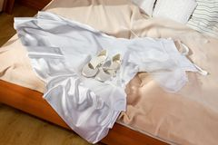 Wedding dress and shoes on the bed Stock Photo