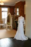 A wedding dress in a shop. With a mirror and chair Stock Images