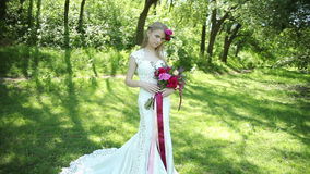 Wedding dress with train. beautiful wedding bouquet of flowers in hands of young bride. weddings. young woman in the park stock video