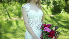 Wedding dress with train. beautiful wedding bouquet of flowers in hands of young bride. weddings. young woman in the park stock video footage