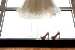 Wedding dress and wedding shoes. Infront of window Stock Photos