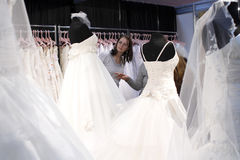 Wedding dresses fair. A woman is searching for a wedding dress at a wedding fair stock photos