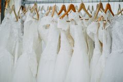 Wedding dresses on hangers. Wedding beautiful white dresses on wooden light brown hangers stock photos