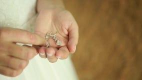 Wedding earrings on a female hand, she takes the earrings, the bride fees morning bride, white dress, wear earrings stock video