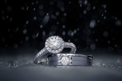 Wedding engagement diamond rings with water drops. Dark background with copy space stock photo