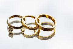 WEDDING AND ENGAGEMENT RING. Pair of golden wedding rings and engagement ring on a mirror background Stock Photography