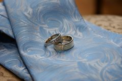Wedding engagement rings. On a blue tie Royalty Free Stock Images