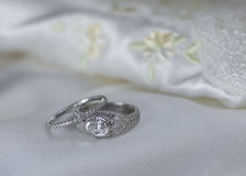 Wedding and Engagement Rings on satin. Hese beautiful rings are white god and studded with diamonds.  Set on elegant satin and lace and embroidery, they are Stock Photo