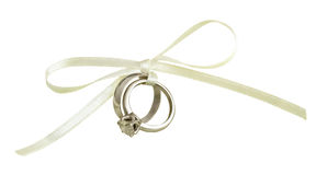 Wedding and engagement rings tied with white silk ribbon stock photos