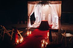 Wedding evening ceremony, venue aisle with candles in glass lanterns and arch, stylish wedding decoration for night ceremony in g. Arden, lights. beautiful stock image