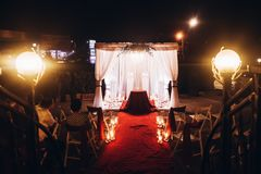 Wedding evening ceremony, venue aisle with candles in glass lanterns and arch, stylish wedding decoration for night ceremony in g. Arden, lights. beautiful royalty free stock image
