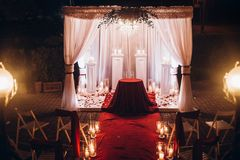 Wedding evening decor for ceremony, venue aisle with candles in. Glass lanterns and arch, stylish wedding decoration for night ceremony in garden, lights royalty free stock photo
