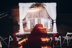 Wedding evening decor for ceremony, venue aisle with candles in. Glass lanterns and arch, stylish wedding decoration for night ceremony in garden, lights stock photos