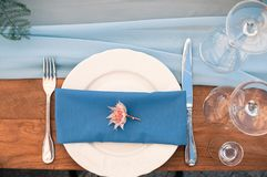 Wedding or Event decoration table setup, blue napkin, outdoor. Closeup view of Wedding or other catered Event setting, flower, white plate, blue napkin, wooden Stock Image