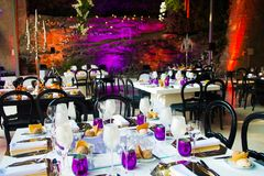 Wedding Dinner, Event Tables, White and Purple Party Decoration. Wedding or event tables decoration in amber, purple, crystal, silver, white and black. Silvery Stock Photo