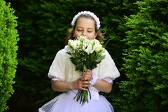 Wedding fashion, beauty salon. Little girl in white dress with rose flower bouquet. Bride girl, bridesmaid and wedding ceremony. Girl child in green summer royalty free stock photos
