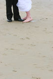 Wedding feet on sand. Front view of wedding couple's feet standing on sandy beach Stock Photography