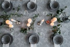 Wedding or festive table setting. Plates, wine glasses, candles and cutlery. Beautiful arrangement Stock Image