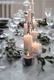 Wedding or festive table setting. Plates, wine glasses, candles and cutlery. Beautiful arrangement Stock Images