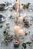 Wedding or festive table setting. Plates, wine glasses, candles and cutlery. Beautiful arrangement Royalty Free Stock Images