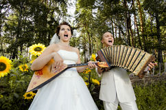Wedding. Fiancee blow the balalaika,  bridegroom play on accordion, wedding  humour photo Stock Image