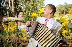 Wedding. Fiancee listen,  bridegroom play on accordion, wedding  humour photo Stock Photo