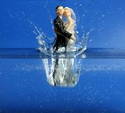 Wedding figurine falling down to blue water Royalty Free Stock Images