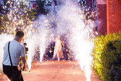 Wedding Fireworks. Wedding Couple Moving Trough Firewoks to Camera Operator and Photographer stock image