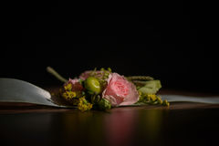 Wedding floral centerpiece with pink rose at its core against a dark background Royalty Free Stock Images