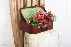 Wedding floral rose decor composition. Shabby chic wedding. Wedding floral decor composition, flowers in vintage brown suitcase at bedside. Old suitcase with stock photo