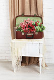 Wedding floral rose decor composition. Shabby chic wedding. Wedding floral decor composition, flowers in vintage brown suitcase at bedside. Old suitcase with stock photos