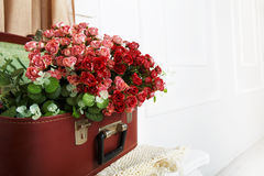 Wedding floral rose decor composition. Unusual wedding floral decor composition - flowers in vintage brown suitcase. Old suitcase with rose flowers. Bouquet of stock image