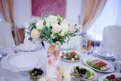 Wedding floristry. Beautiful lush bouquet on the table in restaurant. Table served food and snacks Stock Photo