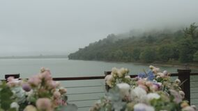 Wedding flower arch and decoration lake and mountains in fog on the background, close - up wedding arch with pink