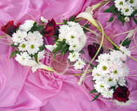 Wedding flower arrangement. Of daises, lilies and roses on a pink silk Stock Image