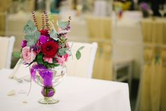 Wedding flower bouquet in glass vase on guest table Stock Photography