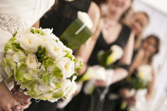 Wedding flower bouquet. Picture of a bride holding her white and green flower bouquet. She is in a row with her maids of honour and they are also holding flowers Stock Photo