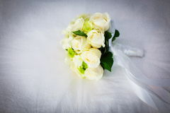 Wedding flower bouquet. Wedding bouquet of white roses on a white veil Stock Photos