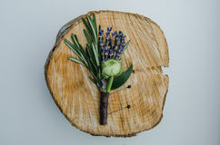 Wedding flower boutonniere with ranunculus, lavender, rosemary on wooden speel. Groom detail, rustic style. Top view. White backgr Royalty Free Stock Photography