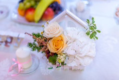 Wedding flower decoration. Event decoration with white hydrangea and yellow roses, withe candle and wooden piece Stock Photos
