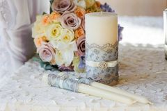 Wedding bouquet with candles. Wedding flower roses and blue delphinium on a table with candles and cloth closeup Stock Photo