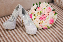 Wedding flower shoes. Wedding flower and shoes on the couch Royalty Free Stock Photography