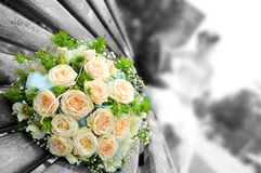 Wedding flowers. The beautiful wedding bouquet flowers lays on a bench, on a background a newly-married couple sit... Focus on a bouquet. gray and color Stock Photo