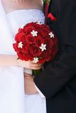 Wedding flowers. The body of a bride and groom with the brides bouquet of red roses Stock Photos