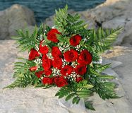 Wedding Flowers. A bouquet of red roses sitting on a rock by the water's edge stock photo